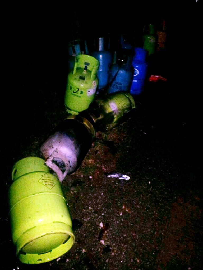 Gas cylinders removed from the slum with rusty gate