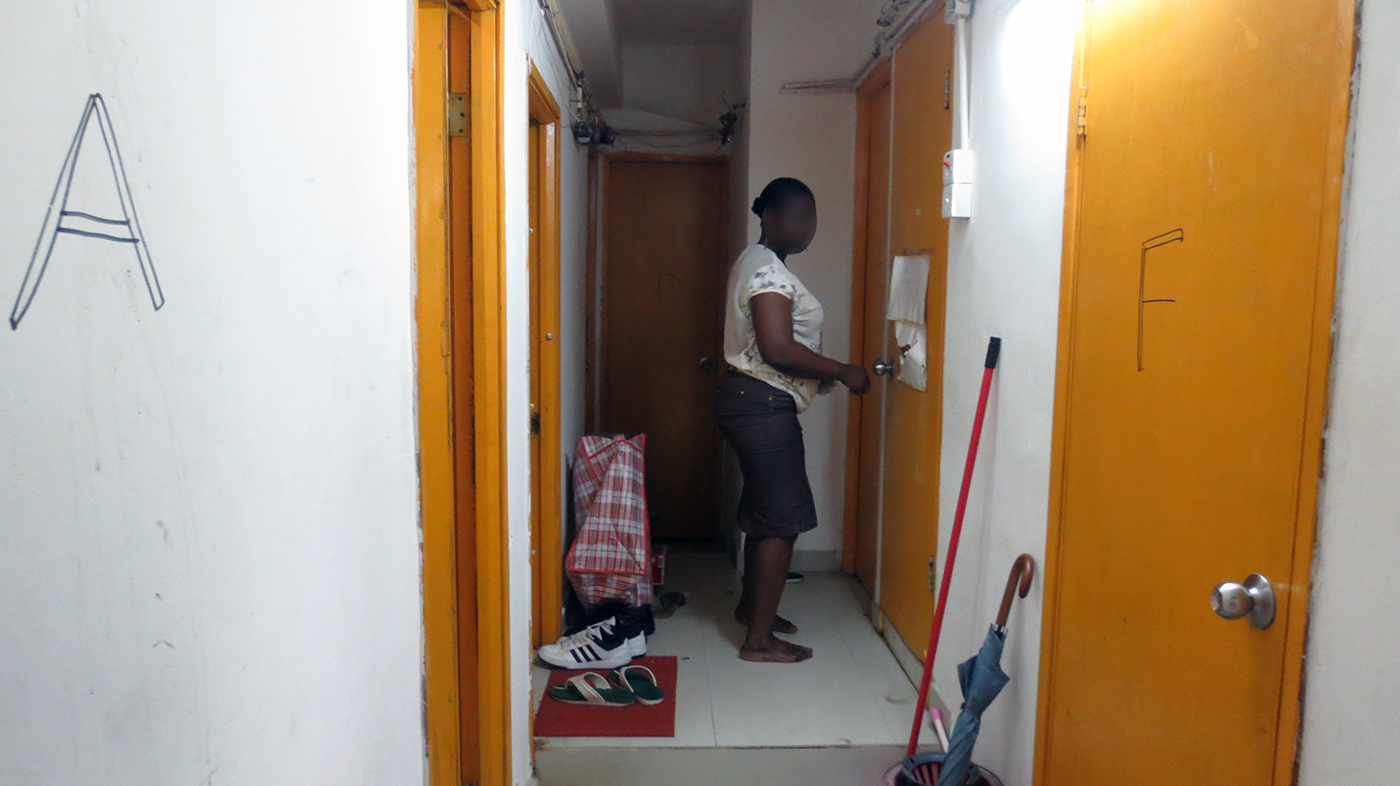 An African refugee enters a subdivided unit in Hung Hom, unrelated to this blog